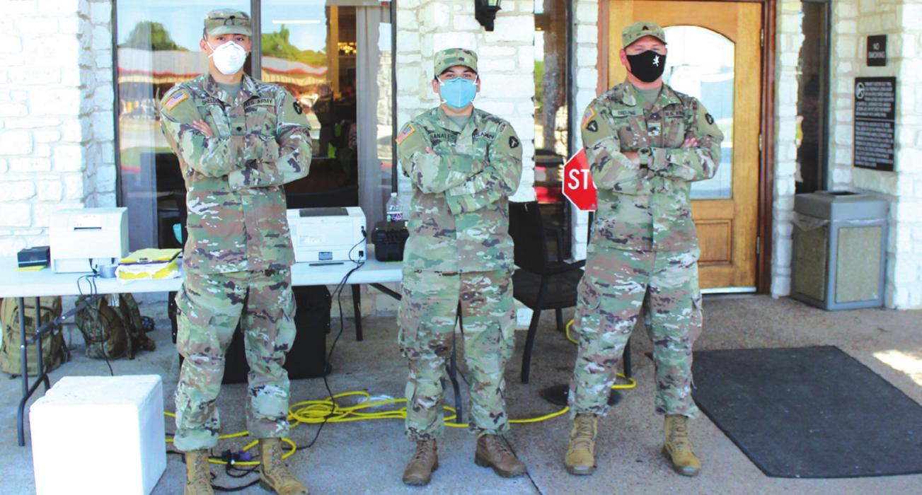Three members of the National Guard pause from their duties Friday during a mass testing event at Monument Hill Nursing Home in La Grange. They had been doing the same thing in Bastrop the day before. Photo by Jeff Wick
