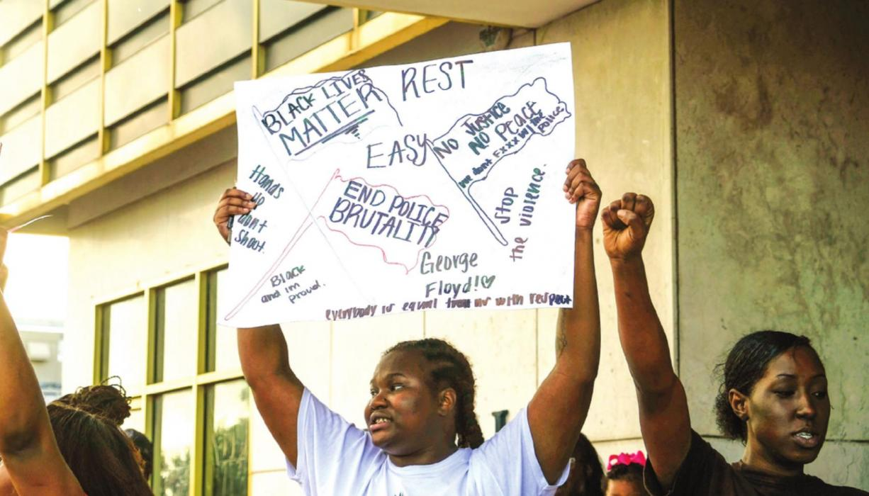 Diamond Houston holds up a sign as other protesters chant in front of Schulenburg City Hall at the Black Lives Matter demonstration in Schulenburg Wednesday evening, June 3. Photo by Andy Behlen