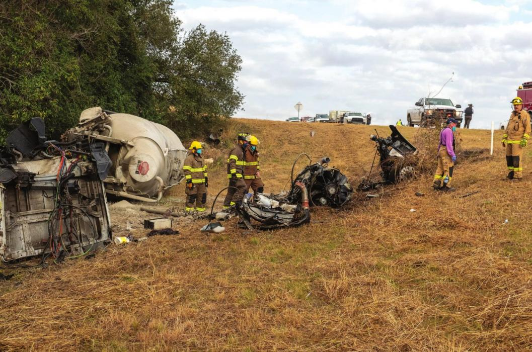 Ellinger firefighters examine the wreckage following an 18-wheeler rollover on SH 71 Monday morning. Photo by Andy Behlen
