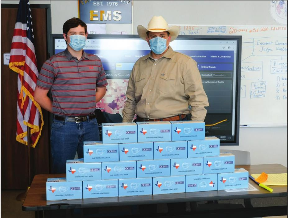 Fayette County Emergency Management Chief Craig Moreau (right) and intern Brendan Gilbreath (left) pose with some of the thousands of face masks that Schulenburg native Carman Kobza provided to the County's emergency management department. Photo by Andy Behlen