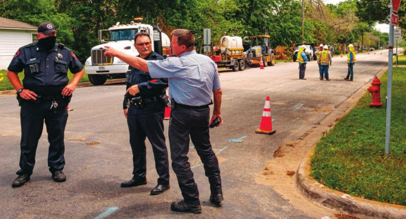 Patrolman Curtis Zwahr and Sgt. Travis Anderson of the La Grange Police Department and La Grange Fire Chief Frank Menefee make plans to evacuate the neighborhood after a gas leak at the corner of Milam and Jackson streets Monday afternoon. A contract crew working for Centerpoint Energy (pictured in the background) accidentally struck a four-inch gas line while digging with an excavator. Photo by Andy Behlen
