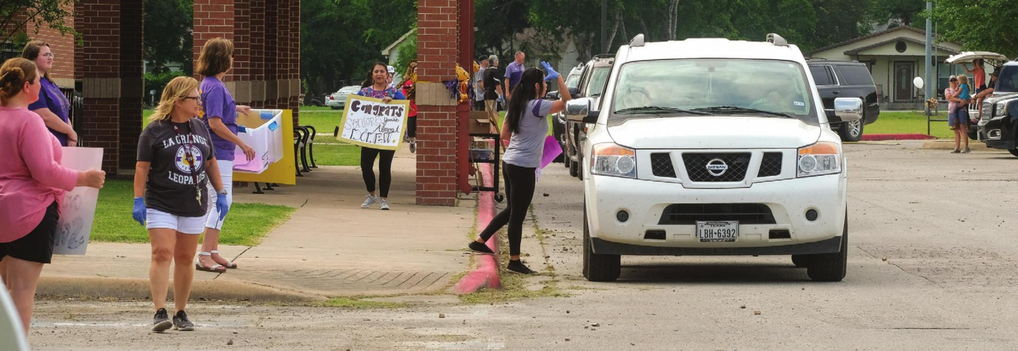 Seniors at La Grange High School picked up their graduation caps and gowns in a drive-through at the school Tuesday, May 5. For most of the students, it was their first visit to campus since spring break, when the school closed for the coronavirus. At the drive-through on Tuesday, teachers and school staff held up motivational signs for the soon-to-be graduates. La Grange ISD has not yet announced plans for a graduation ceremony. Seniors were told to expect a ceremony date in June. Photo by Andy Behlen