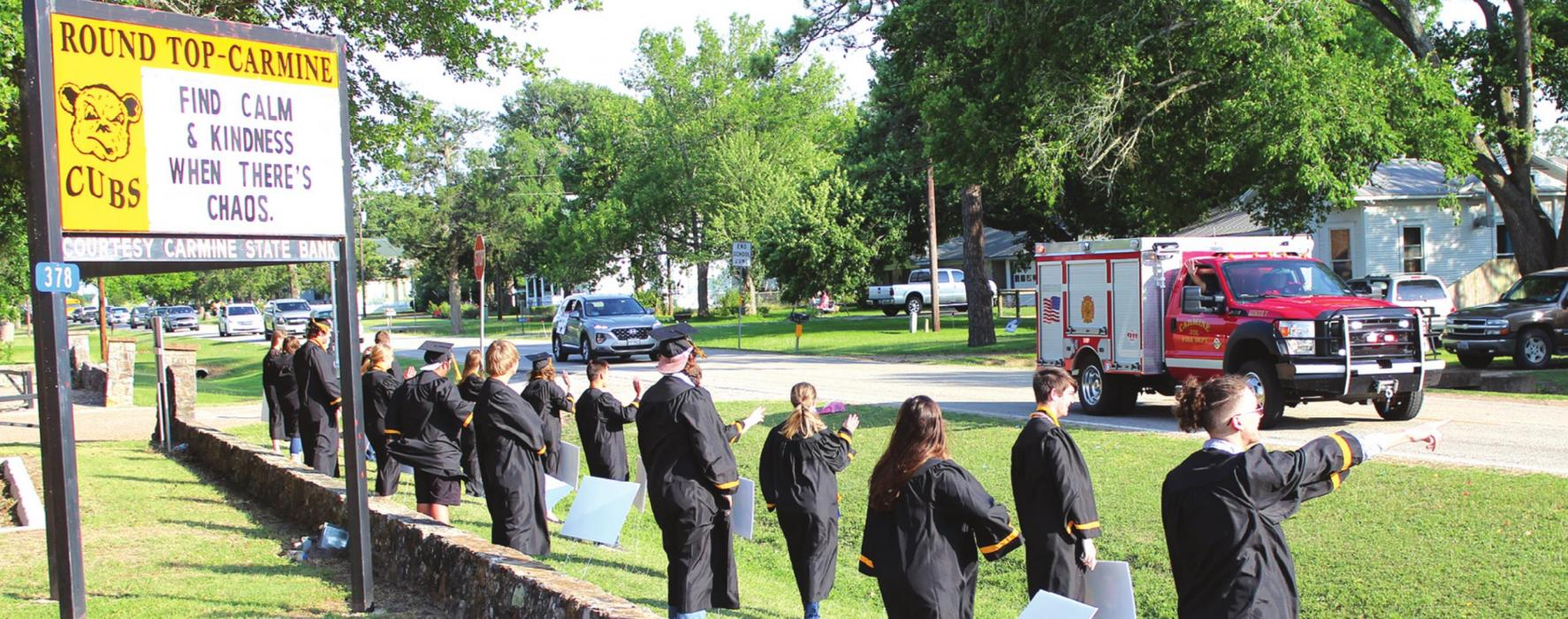 Members of the Round Top-Carmine senior class watch and wave as nearly 100 vehicles, many decorated with signs, balloons, etc, rolled by the high school campus to cheer on the graduates. The event was organized to make up for some of the other senior events the class was going to miss out on because of coronavirus precautions. Photo by Jeff Wick