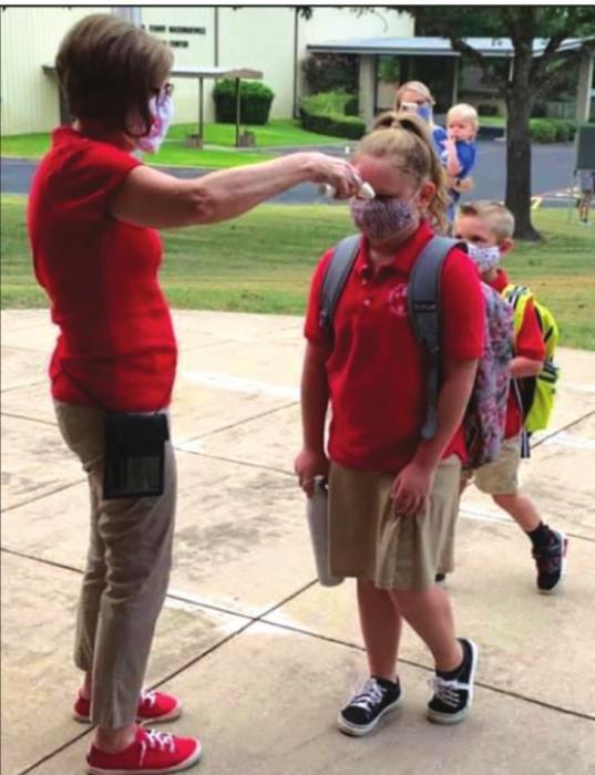 Sacred Heart School secretary Cindy Fletcher checks students' temperatures as they walk in on the first day of school Thursday.
