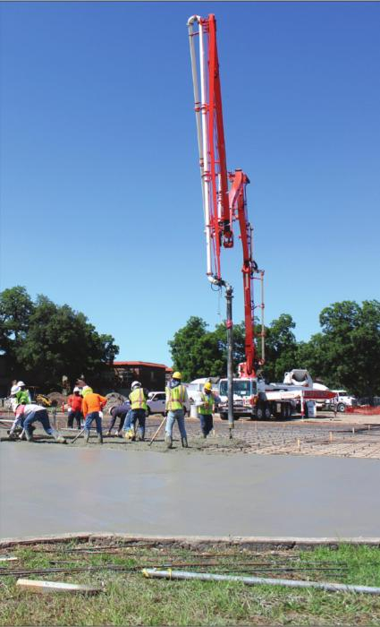 Several people were hard at work Monday smoothing out a steady stream of concrete in the new school parking lot on the corner of Vail and Jackson Streets in La Grange. Photo by Jeff Wick