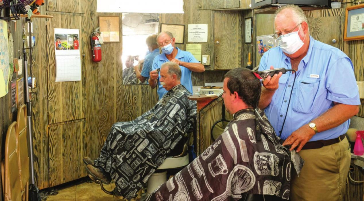 Barbers Ken Jurecka and Floyd Weishuhn were back in business on the La Grange Square Friday morning. Barber shops and salons have been closed for nearly two months during the coronavirus pandemic. Photo by Andy Behlen