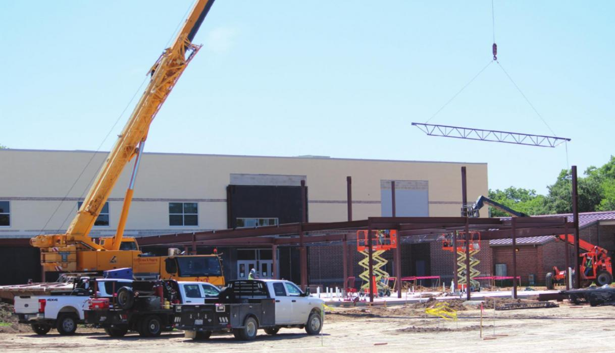 A metal support piece is lowered into place by a crane in what is a very active construction site at what will be the new west-facing entrance to the La Grange elementary complex. Photo by Jeff Wick