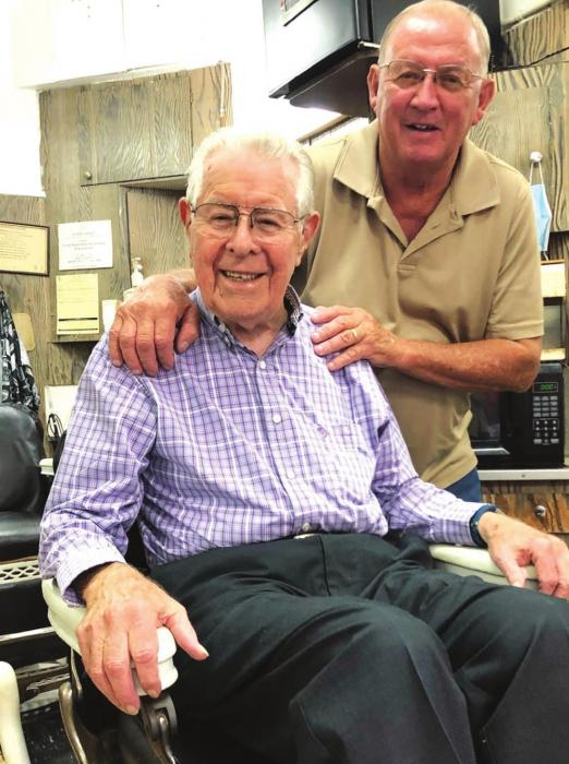 When Ken moved to his new barbershop, he relocated his two 106-year-old antique barber chairs and the mirrors behind them. The chairs, which were manufactured by Emil Paidar Co. of Chicago in the early 1900s, have stood the test of time as both Ken (standing) and Charlie (seated) attested. (Elaine Thomas shot this photo several weeks before the state and citywide masking order.)