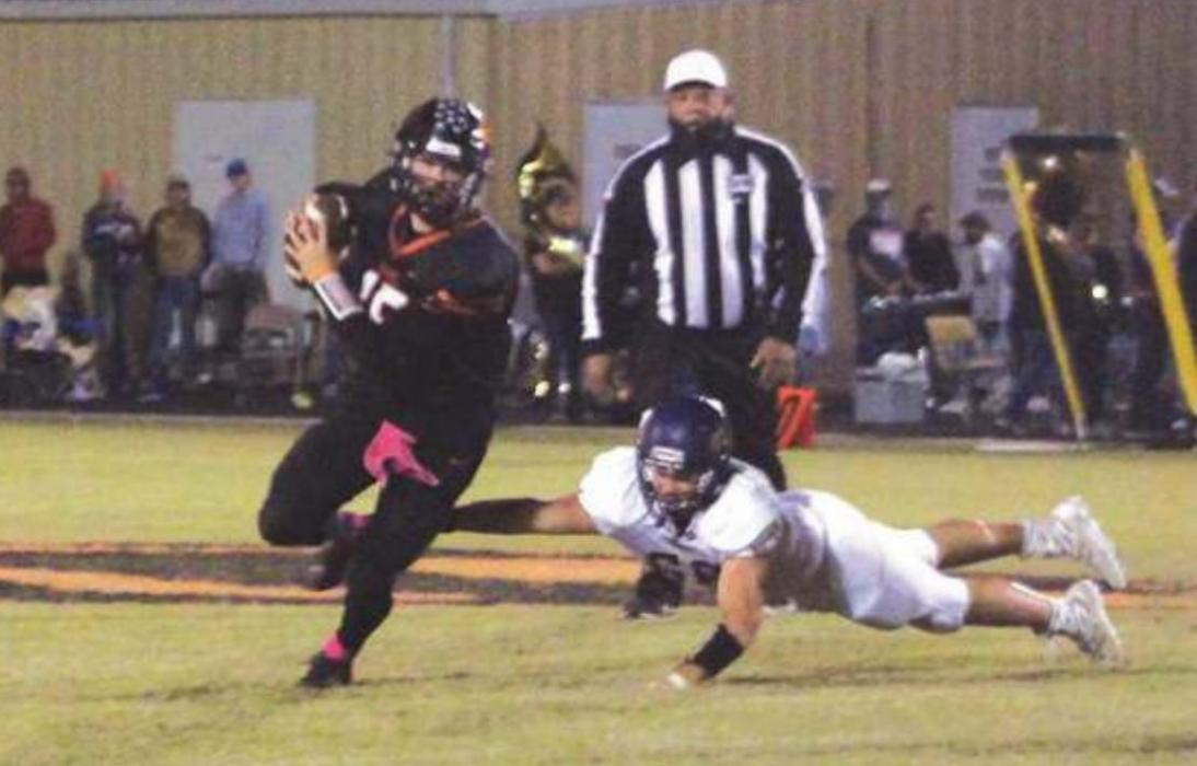 Schulenburg quarterback Brett Janecek scrambles away from this Shiner defensive player Friday. Photo by Brian Pierson